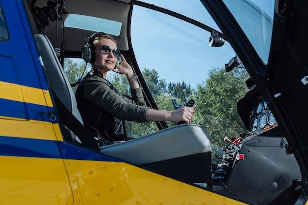 Lubi latać. wspaniała młoda pilotka siedząca w kabinie pilota helikoptera i pozująca do kamery, trzymając kierownicę