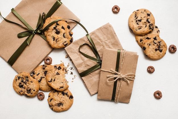 Lubi słodycze i prezenty na święta. małe eleganckie prezenty na białym stole z domowymi bułeczkami czekoladowymi w pobliżu, zdjęcie z góry