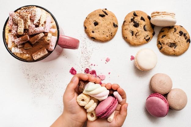 Lubi słodycze i prezenty świąteczne. nierozpoznane dziecko z kolorowym makaronikiem i zefirami w dłoniach, czekoladową bułeczką i pysznym kakao z pianką na białym stole w pobliżu, widok z góry