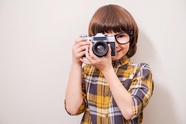 Lubi strzelać. mały chłopiec w okularach trzymający aparat i uśmiechający się stojąc na szarym tle