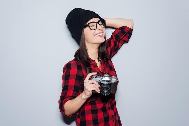 Lubi strzelać. piękna młoda kobieta w nakryciu głowy i okularach trzymająca aparat i trzymająca zamknięte oczy, stojąc na szarym tle
