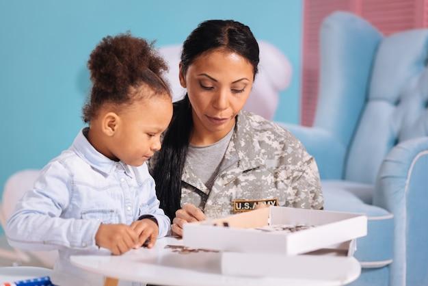 Lubiane zagadki. urocza, skupiona inteligentna mama i córka siedzą przy stole i cieszą się wspólnym hobby, podczas gdy matka spędza wakacje w domu