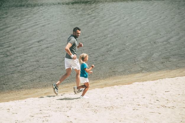 Lubię biegać na świeżym powietrzu. widok z góry na wesołego ojca i córkę w sportowych ubraniach biegających razem nad brzegiem rzeki