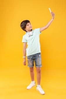 Lubię fotografować. zadowolony szczupły chłopiec w słuchawkach i robieniu selfie