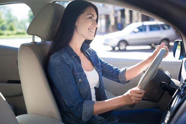 Lubię prowadzić. radosna pozytywna ładna kobieta trzyma kierownicę i uśmiecha się podczas jazdy samochodem