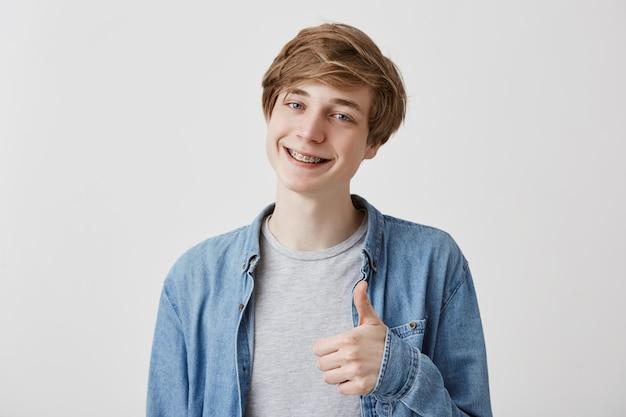 Lubię to. dobra robota. szczęśliwy młody jasnowłosy mężczyzna w dżinsowej koszuli robi kciuki do góry i uśmiecha się wesoło z szelkami, pokazując swoje wsparcie i szacunek dla kogoś. język ciała