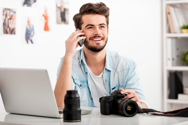 Lubię twórczą pracę. szczęśliwy młody człowiek rozmawia przez telefon komórkowy i uśmiecha się siedząc w swoim miejscu pracy i trzymając aparat cyfrowy
