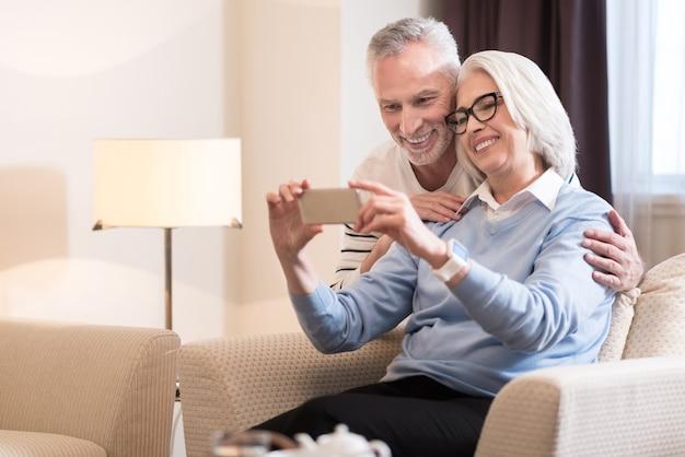 Lubimy gadżety. wesoła, uśmiechnięta para w wieku, biorąc selfie, siedząc na kanapie i wyrażając szczęście