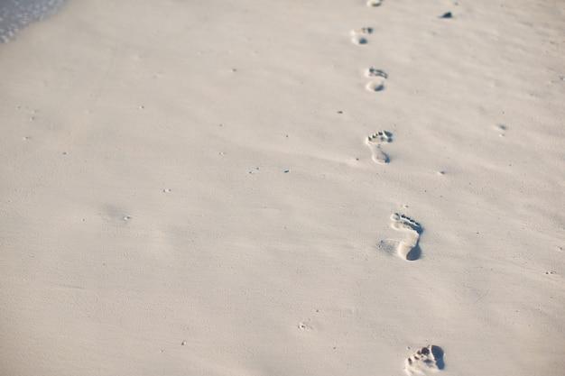Ludzcy odciski stopy na białej piasek plaży