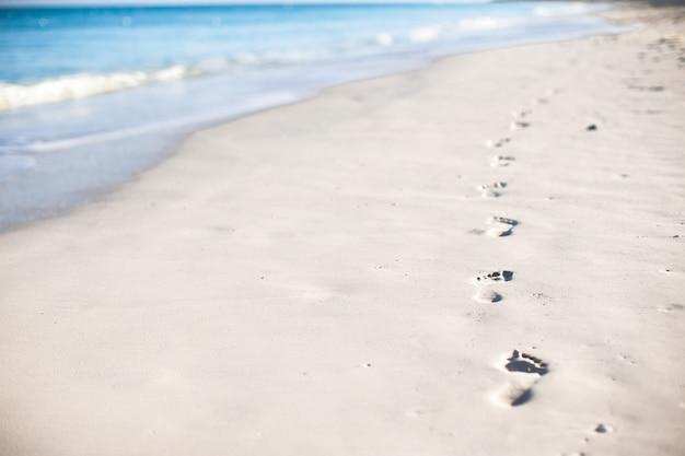 Ludzcy odciski stopy na białym piasku wyspa karaibska