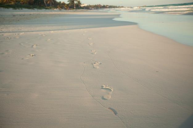 Ludzcy odciski stopy na tropikalnej białej piasek plaży w tulum, meksyk
