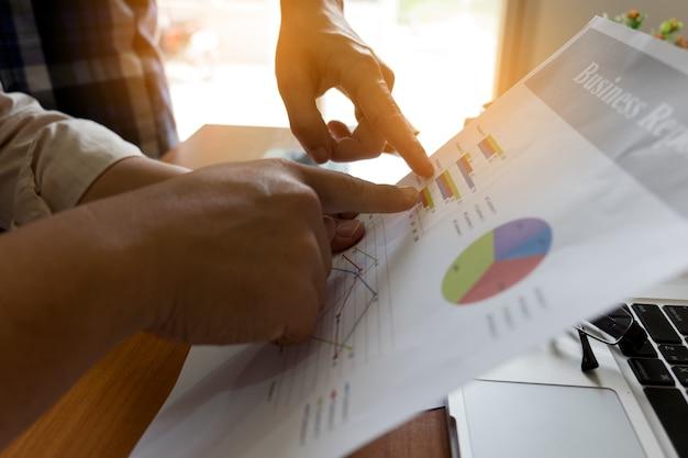 Ludzi biznesu burzy mózgów w biurze, analizują sprawozdania finansowe i wskazują na dane finansowe na arkuszu