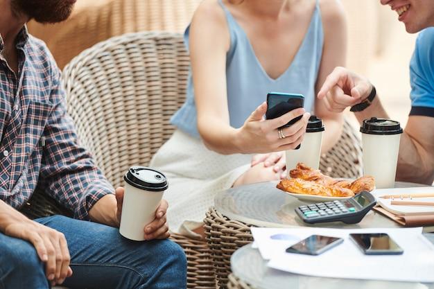 Ludzi biznesu omawiających obraz na ekranie smartfona