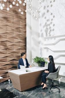 Ludzi biznesu omawiania strategii inwestycyjnej na spotkaniu w nowoczesnym biurze
