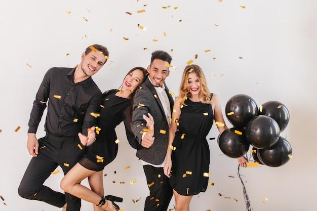 Ludzie bawią się na imprezie z czarnymi balonami i konfetti