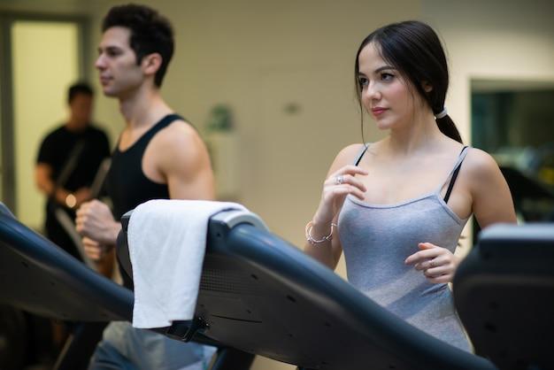 Ludzie biegający na bieżni w siłowni
