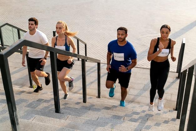 Ludzie biegnący po schodach w pełnym ujęciu