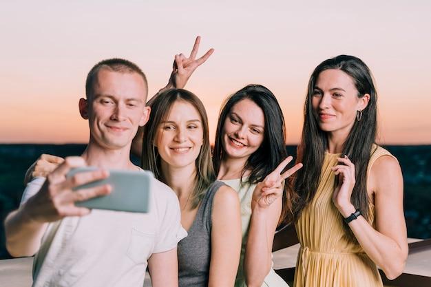 Ludzie biorący selfie na dachu o świcie
