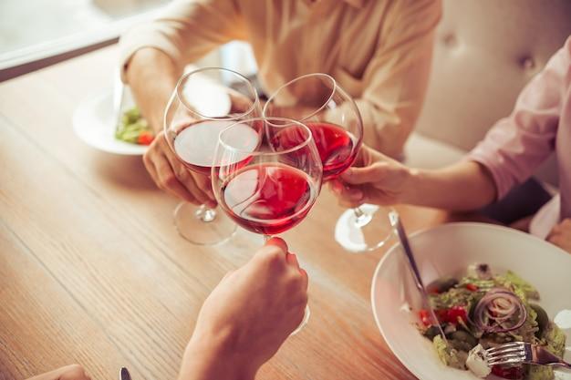 Ludzie biznesu brzęczą szklanki wina razem.