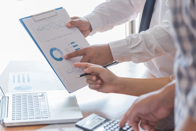 Ludzie biznesu burzy mózgów na biurku, analizują raporty finansowe i wskazując dane finansowe na arkuszu