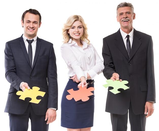 Ludzie biznesu chcą razem puzzle na białym tle.
