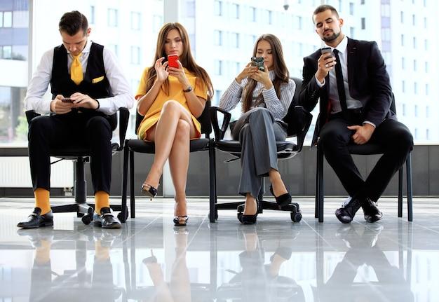 Ludzie biznesu czekają na rozmowę kwalifikacyjną w biurze