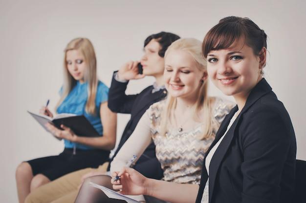 Ludzie biznesu czekają w kolejce siedząc w rzędzie trzymając smartfony i cvs