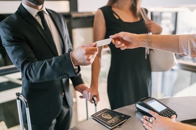 Ludzie biznesu dokonują płatności kartą przy zameldowaniu w recepcji.
