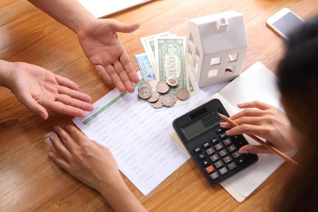 Ludzie biznesu dyskutują z kalkulują dane finansowe na drewnianym biurku