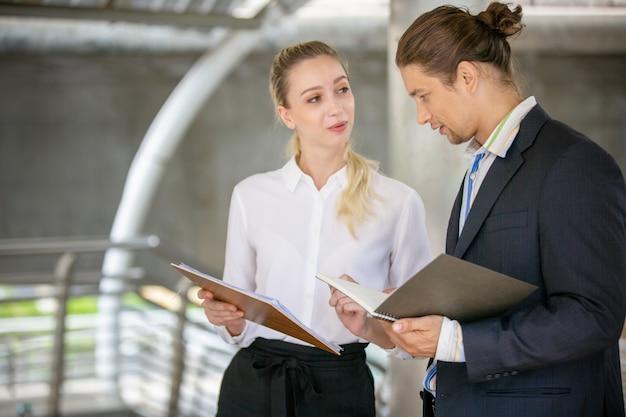 Ludzie biznesu dyskutuje nad schowkiem i podczas gdy chodzący na zewnątrz biura