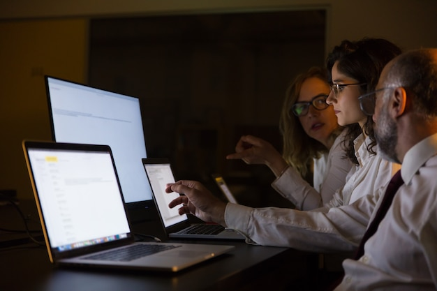 Ludzie biznesu dyskutuje pracę w ciemnym biurze