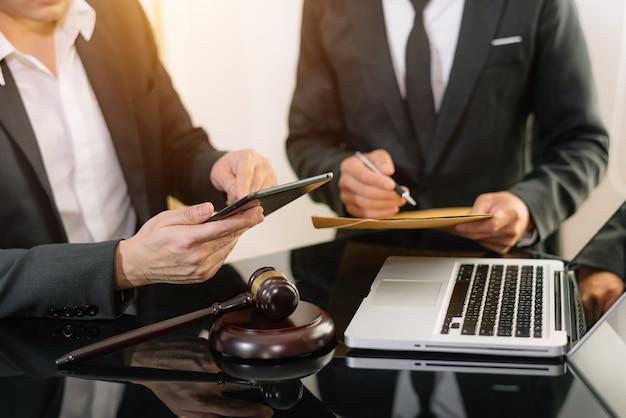 Ludzie biznesu i prawnicy, omawiając dokumenty umowy, siedząc przy stole. koncepcje prawa, porady, usługi prawne. w porannym świetle
