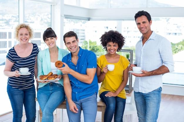 Ludzie biznesu jedzenie pączków i picie