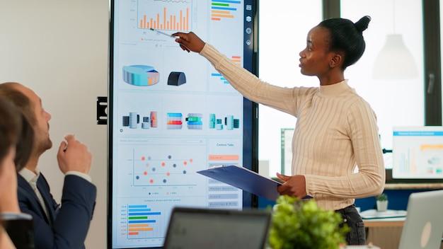 Ludzie biznesu korporacyjnego spotykający się w sali konferencyjnej, afrykański menedżer podczas burzy mózgów z kolegami, omawianie strategii, dzielenie się problemami, rozwiązywanie pomysłów współpracujące w sali konferencyjnej firmy