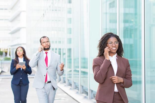 Ludzie biznesu korzystający z cyfrowych gadżetów na zewnątrz