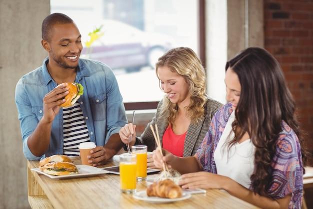 Ludzie biznesu ma śniadanie w jaskrawym kreatywnie biurze