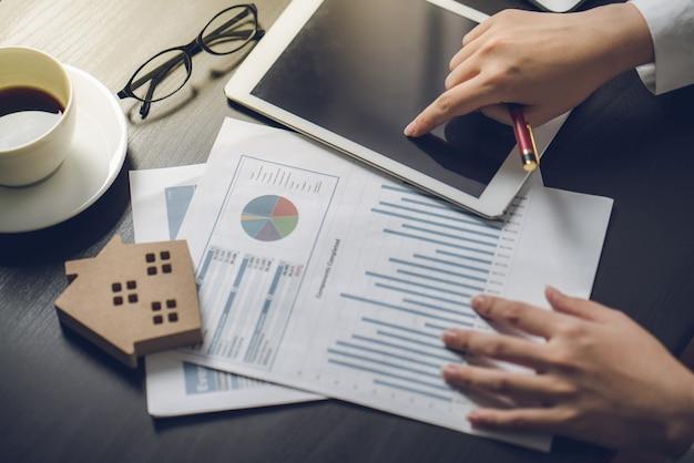 Ludzie biznesu obliczają odsetki, podatki i zyski, aby inwestować w nieruchomości i dom