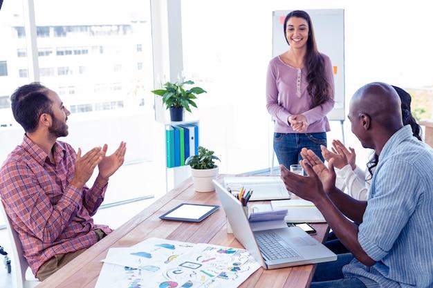 Ludzie biznesu oklaskuje dla żeńskiego współpracownika w kreatywnie biurze