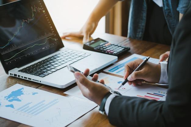 Ludzie biznesu omawiają wykresy i wykresy pokazujące wyniki udanej pracy zespołowej. analizują wykresy inwestycyjne za pomocą laptopa