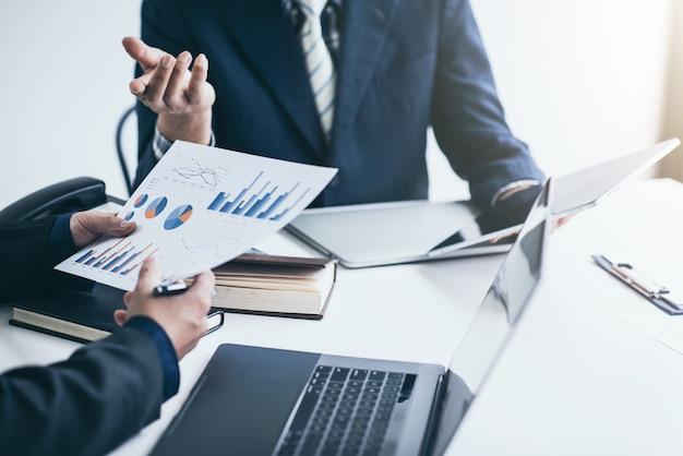 Ludzie biznesu omawiają wykresy i wykresy przedstawiające wyniki ich udanej pracy zespołowej w biurze.