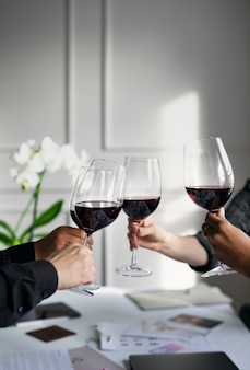 Ludzie biznesu opiekający czerwone wino w biurze