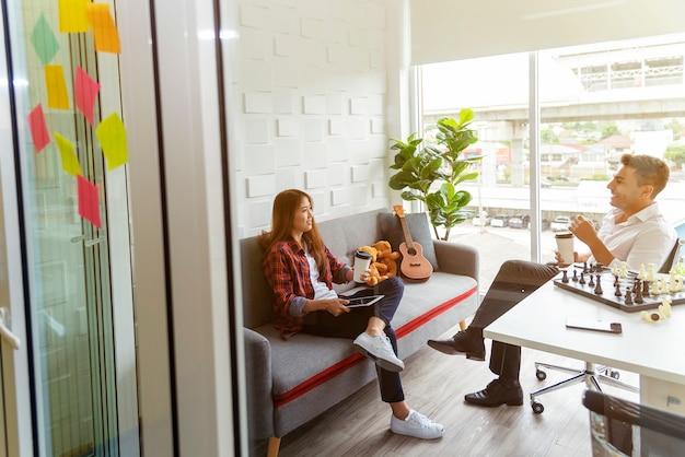 Ludzie biznesu opowiada z relaksują w nowożytnym biurze podczas gdy kawowa przerwa.