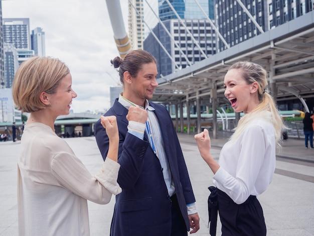 Ludzie biznesu osiągają cele, szczęśliwy zespół biznesu świętuje zwycięstwo w mieście