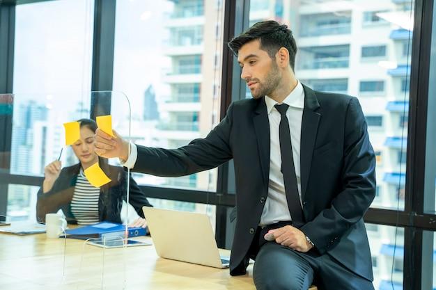 Ludzie biznesu planowania strategii na ścianie z naklejkami w biurze.