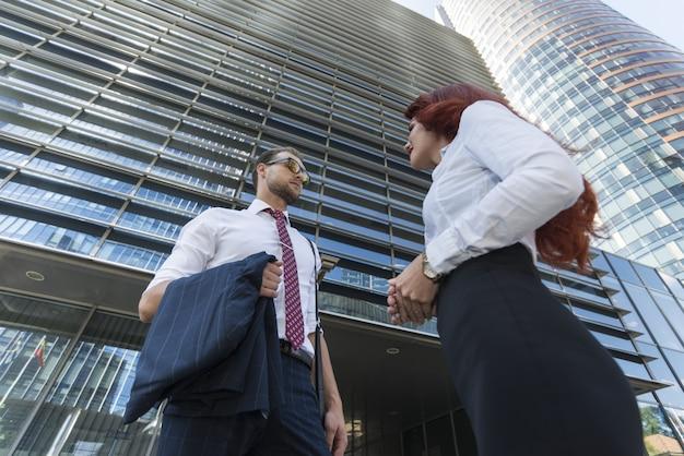 Ludzie biznesu po rozmowie przed swoim biurem, perspektywa ultrawide