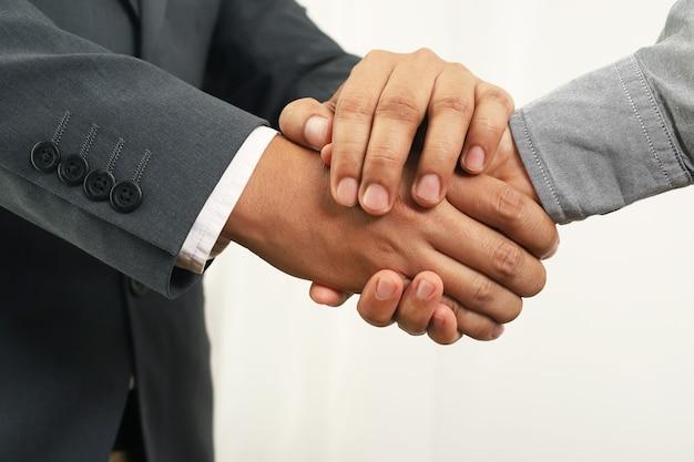 Ludzie biznesu podają sobie ręce, aby zakończyć spotkanie firmowe
