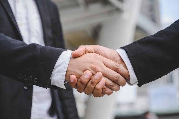 Ludzie biznesu podają sobie ręce aby zawrzeć umowę dotyczącą propozycji biznesowej.