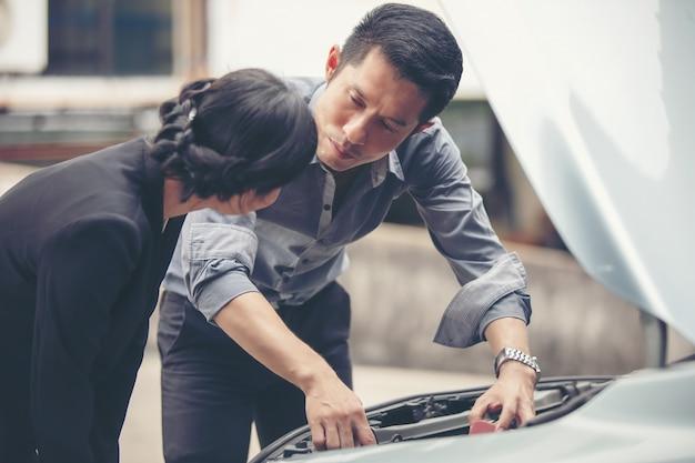 Ludzie biznesu pomagają kobietom w biznesie sprawdzać i naprawiać uszkodzone samochody
