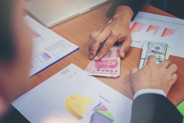 Ludzie biznesu posiadający dolary usd, juan rmb dzielenie pieniędzy na inwestycje giełdowe. wojna handlowa