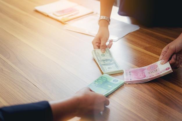Ludzie biznesu posiadający dolary usd, juan rmb, dzielenie pieniędzy w euro na inwestycje giełdowe